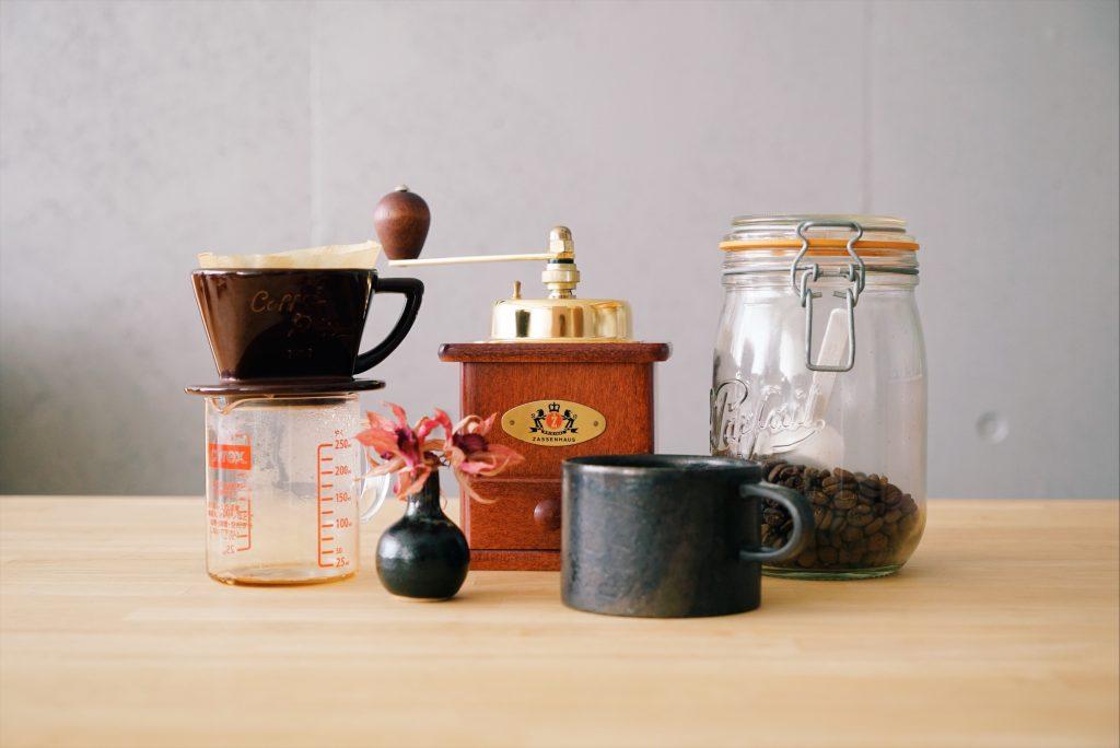 コーヒーミルとコーヒー豆とドリッパーとマグカップ